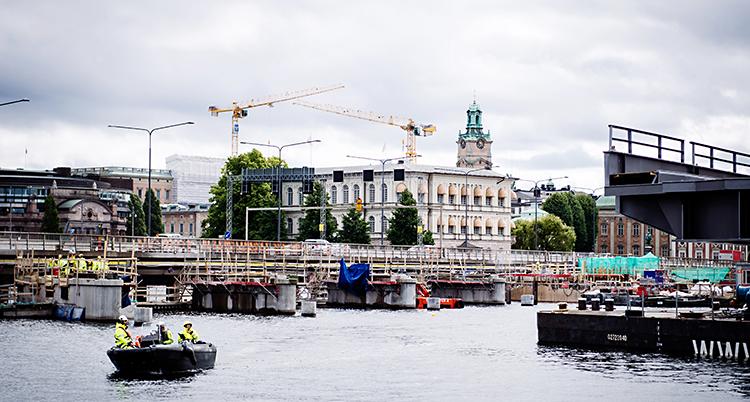 Bilden är tagen mitt i Stockholm. Det är en bro som går över vatten. Där är det folk som jobbar.