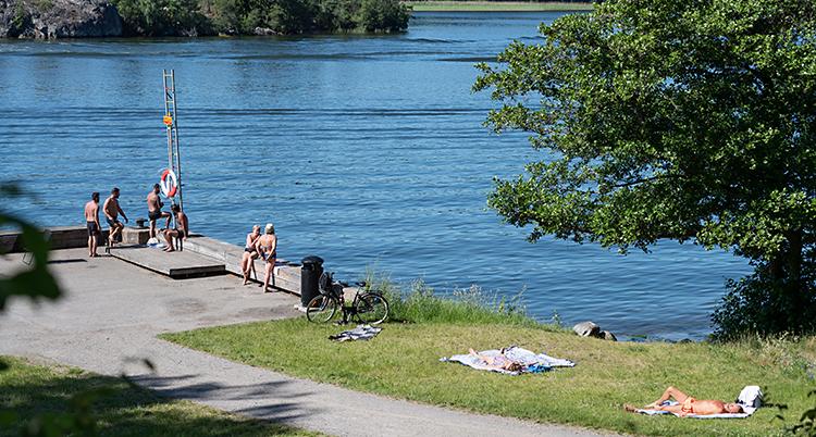 Vi ser en badplats. Människor ligger på gräset och solar. En del står på bryggan vid vattnet. Solen skiner. Det är sommar.
