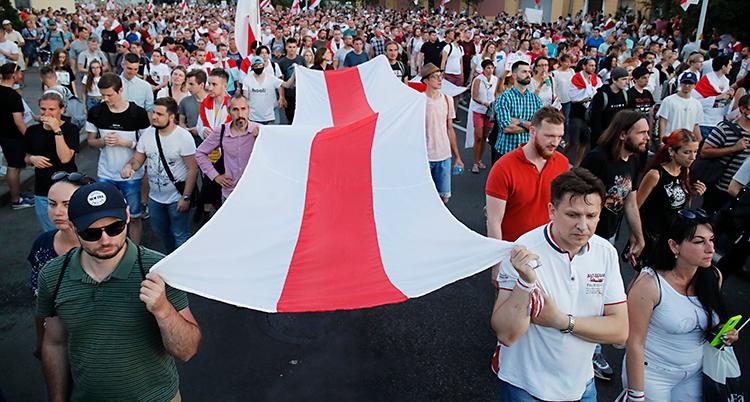 En stor grupp människor är ute på gatan. Några av dem bär på en flagga som är vit och röd.