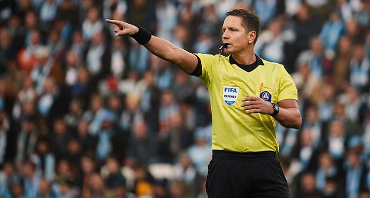 Bilden är tagen på en match i fotboll. Vi ser en domare som pekar med ena handen. Och han blåser i en visselpipa. Han har svarta shorts och gul t-shirt. I bakgrunden syns publiken.