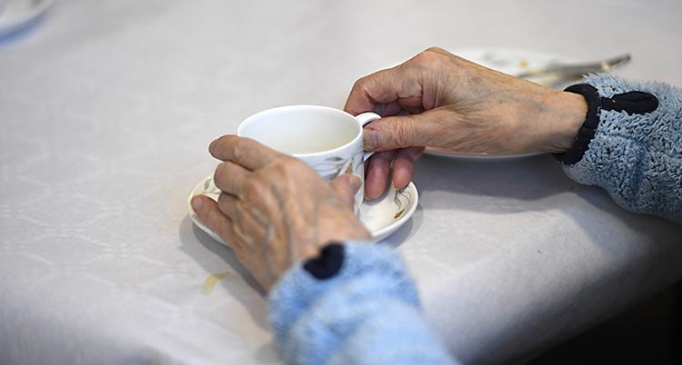 En gammal person sitter och dricker kaffe. Vi ser bara armarna, händerna och en kaffekopp.