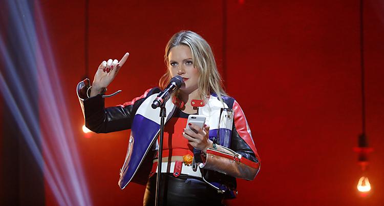 Bilden är från Grammisgalan. Tove Lo är på scenen. Hon har fått ett pris. Hon håller ett tal i mikrofonen. Hon läser talet från sin mobiltelefon.