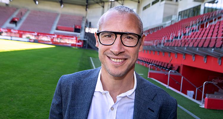 Henrik Larsson ler mot kameran. Han står på en fotbollsarena. Han har kort hår och glasögon. Han har vit skjorta och kavaj.