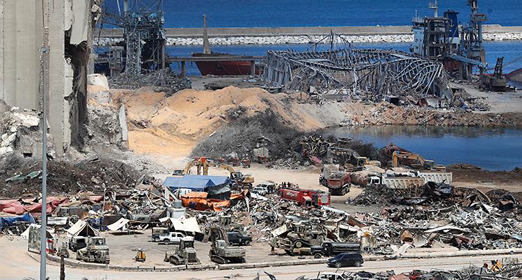 Bilden visar hamnen i staden Beirut. Det har varit en stor explosion. Mycket är förstört. Längst bort syns havet.
