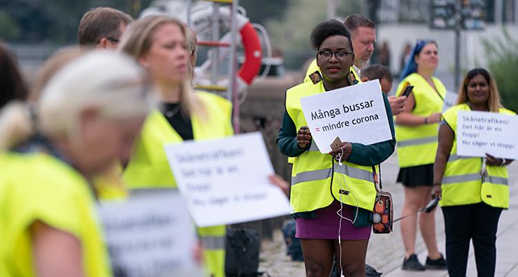 Bilden är tagen utomhus. Vi ser personer som protesterar. De har gula västar på sig. Och skyltar där det står olika saker.