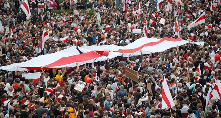 Människor fotade uppifrån som trängs på ett torg med flaggor.