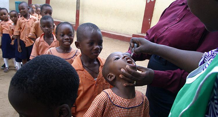 barn står på rad för att få vaccin. Barnet längst fram i kön får vaccin i munnen av en vuxen. Barnen är i sexårsåldern. De har alla samma röda skoluniform.
