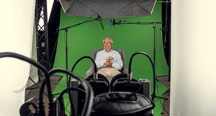 Tobias Rawet i en studio framför en green screen. Han skrattar. Sitter omgiven av tekniska prylar.