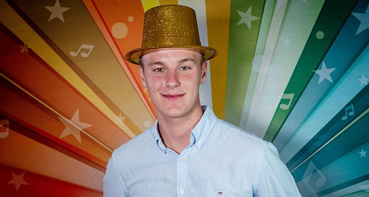 Han står mot en vägg med regnbågens färger. Han har på sig en ljus skjorta och en guldhatt.