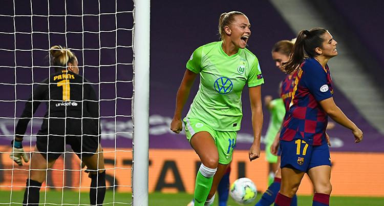 Bilden är från en match i fotboll. En kvinna med blont hår och gröna kläder jublar. En motståndare ser ledsen ut.