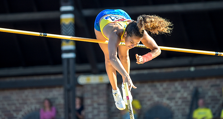 En kvinna hoppar stavhopp. Hon har precis kommit över ribban. Nu är hon på väg att släppa sin stav.