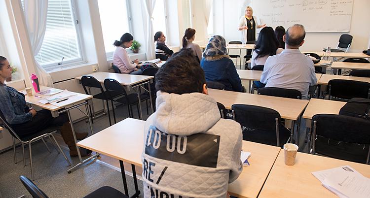 Vi ser ett klassrum. En lärare står vid tavlan och pratar. Elever sitter i bänkar och lyssnar.