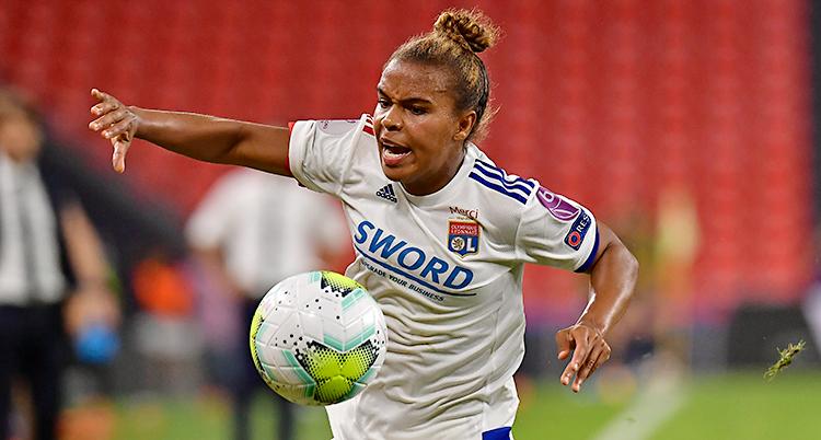 Bilden är från en match i fotboll. En kvinna i vit tröja försöker få med sig bollen.