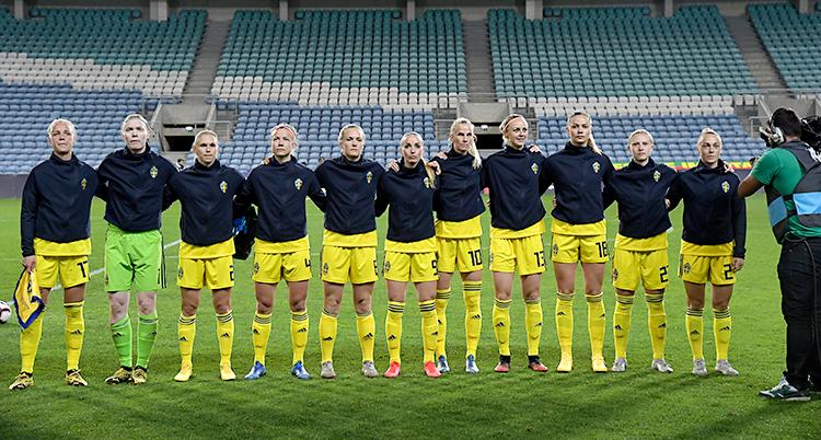 Det svenska laget står bredvid varandra. De är på en fotbollsplan. Snart ska en match börja. De har blå tröjor och gula shorts.