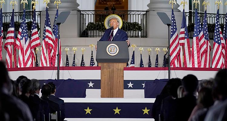 Donald Trump står i en talarstol. Han pratar i en mikrofon. Bredvid honom finns flera amerikanska flaggor. I bakgrunden syns Vita huset.
