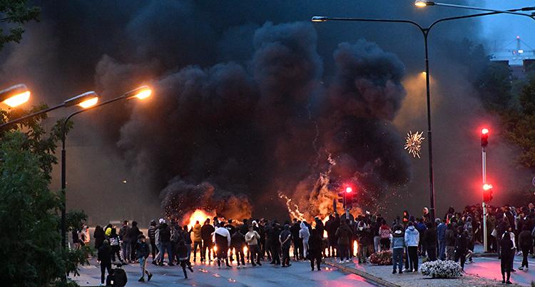 Flera personer har samlats på en gata. Mitt i gatan är det eldar. Det kommer mycket rök.