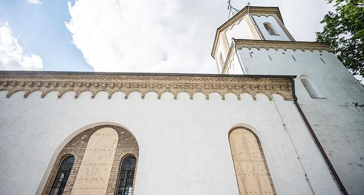 Den vita kyrkan har fått träskivor för fönstren.