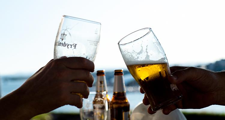 Två personer skålar med öl i sina ölglas. Det är en vacker sommardag.