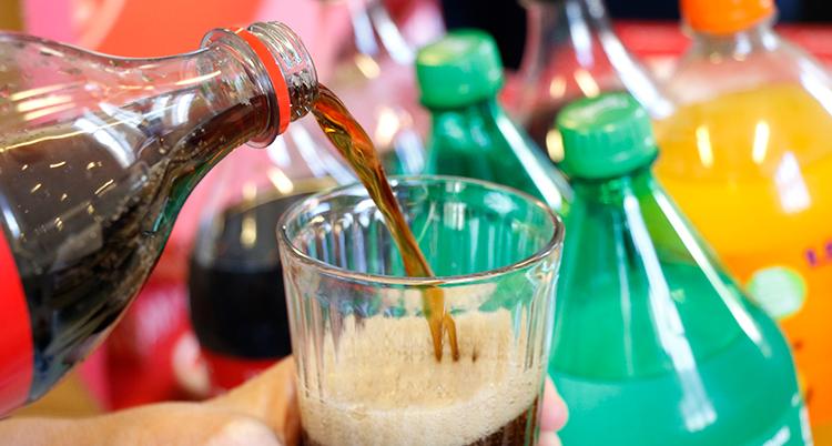 Någon häller upp coca cola i ett glas.