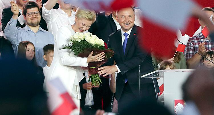 Andrzej Duda och hans fru får blommor av folk som stödjer Duda. De ser glada ut och människor i bakgrunden viftar med flaggor. Bilden är från valdagen den 12 juli.