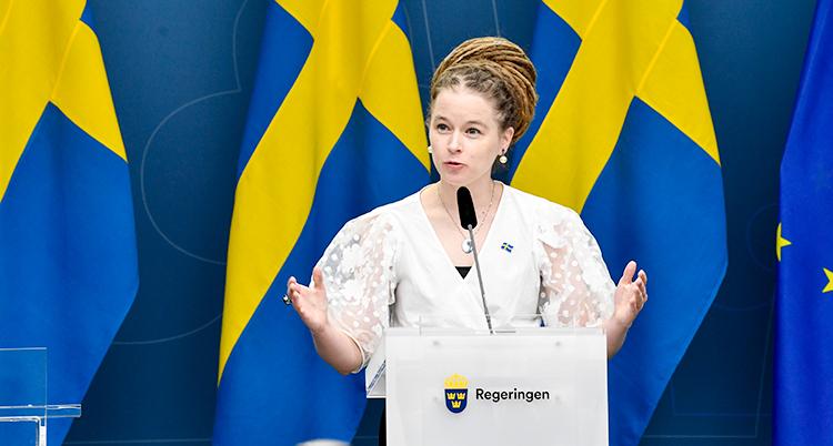 Kulturminister Amanda Lind pratar på en presskonferens. Bakom hennes syns en svensk flagga.