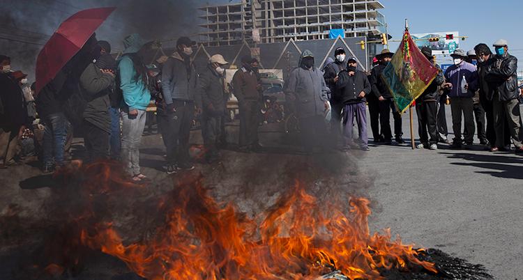 Några demonstranter i Bolivia bränner bildäck. Bakom elden syns en grupp demonstranter som står i en klunga.
