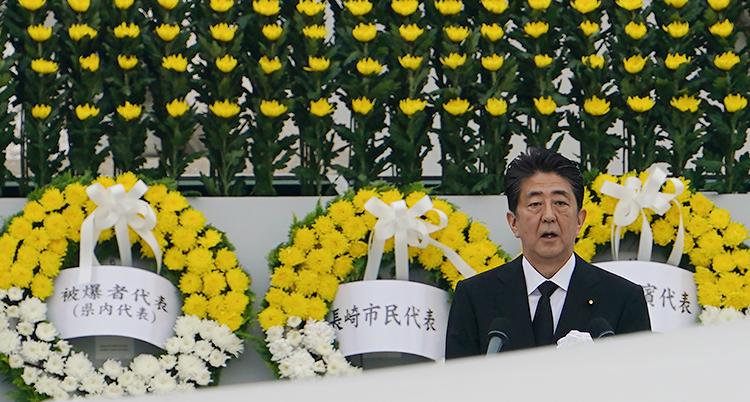 Japans premiärminister Shinzo Abe håller tal. Bakom honom hänger kransar med gula och vita blommor.