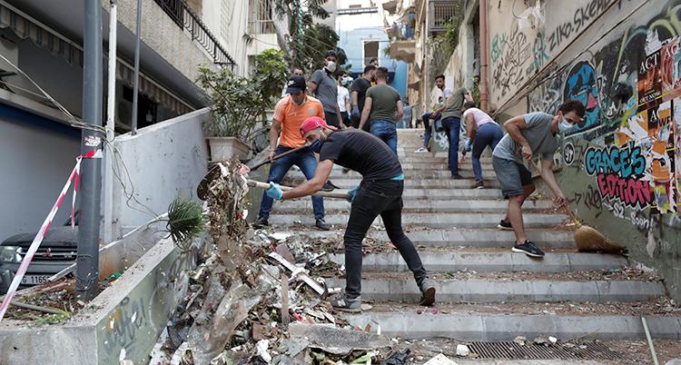 Flera människor röjer upp på en förstörd gata i Beirut.