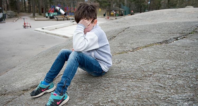 Barnet sitter på marken med ansiktet i sin hand.