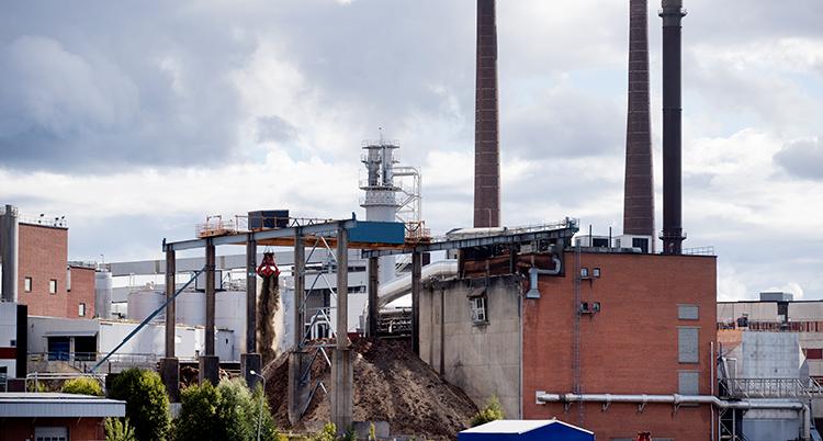 En bild tagen långt ifrån fabriken. Den har flera skorstenar.