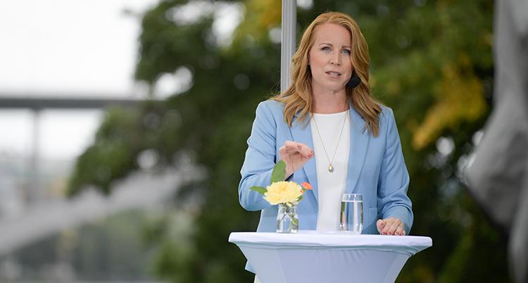 Annie Lööf står i en talarstol utomhus. Hon har blå kavaj. Framför henne står en blomma och ett glas vatten.