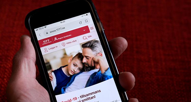 En hand med en mobil. Där syns sajten 1177 för sjukvård.