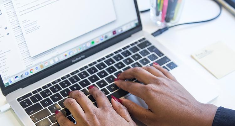 Händer knappar på ett tangentbord.