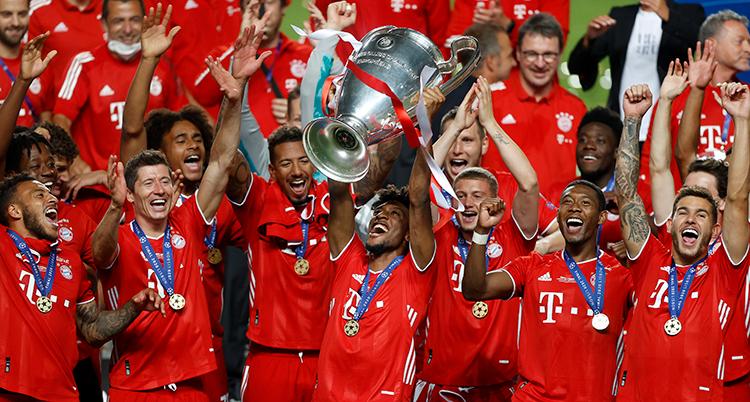 Spelare i röda dräkter skrattar och jublar. En lyfter en stor pokal. Alla har medalj rnt halsen.