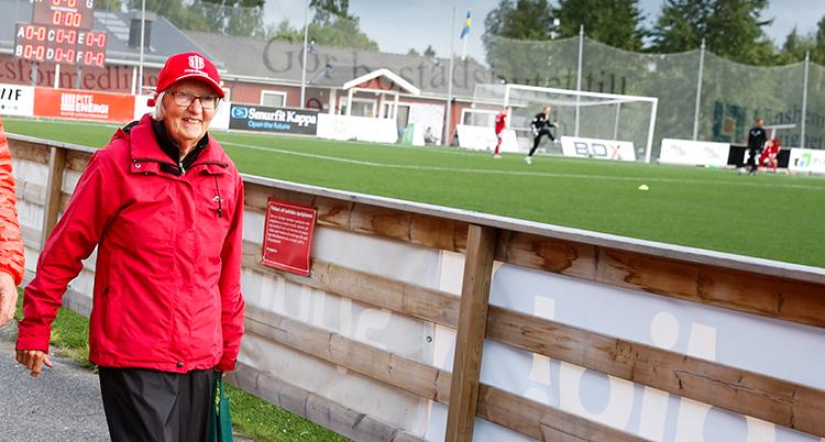 Berit i röd jacka och keps ler och går bredvid fotbollsplanen.