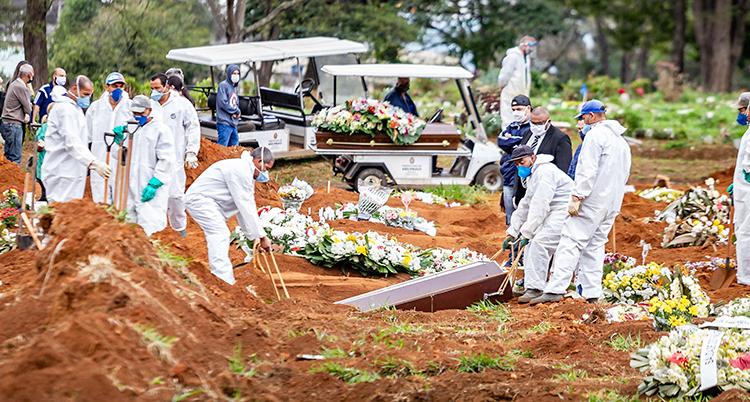 Människor i vita overaller sänker ner en kista i en grav. De har skyddskläder på sig. I bakgrunden är en bil med ännu en kista.