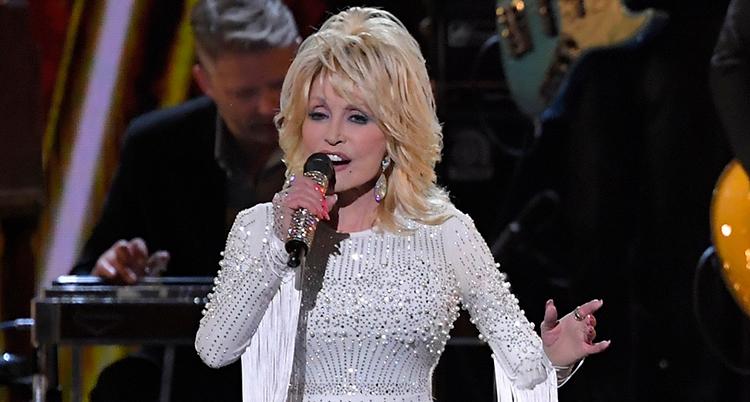 Dolly Parton sjunger i en mikrofon som hon håller i handen.