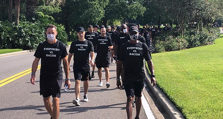 En lång rad med med i svarta tröjor går i en park. På tröjorna stor det Everyone vs. Racism.