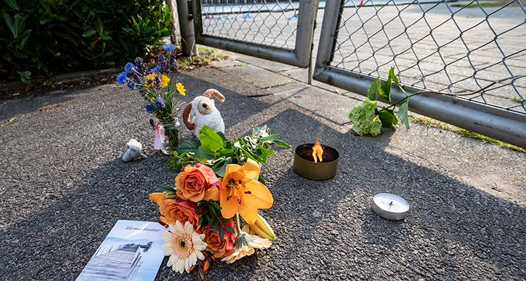 Blommor, ljus och nallar står på asfalten.