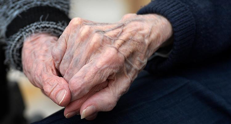Två gamla personer håller varandra i handen.