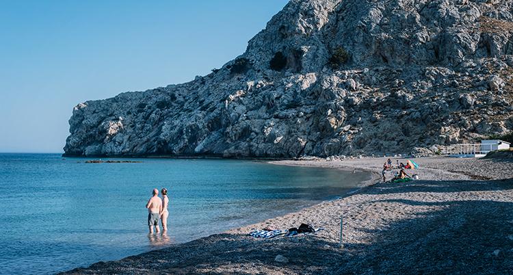 Två personer står ute i vattnet vid en ganska tom strand. Bakom dem är ett berg. Solen skiner.