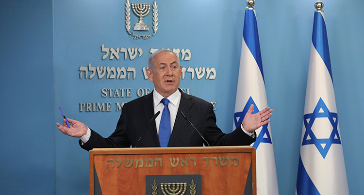 Netanyahu står i en talarstol. Bakom honom är israeliska flaggor.