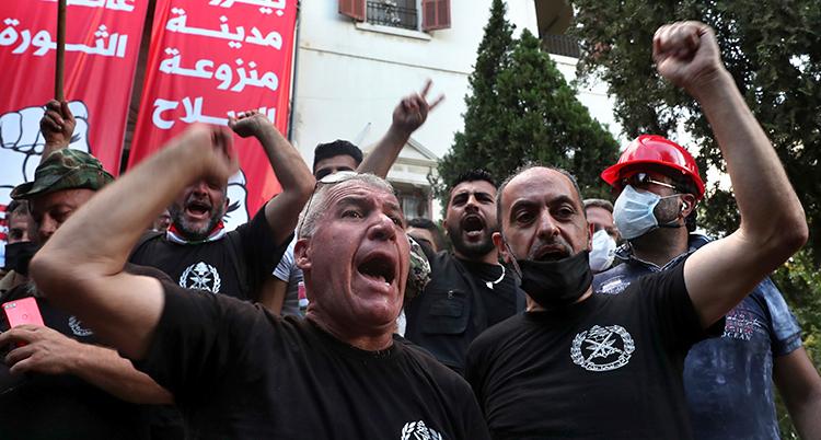 Två arga män knyter sina nävar. I bakgrunden flera andra människor.
