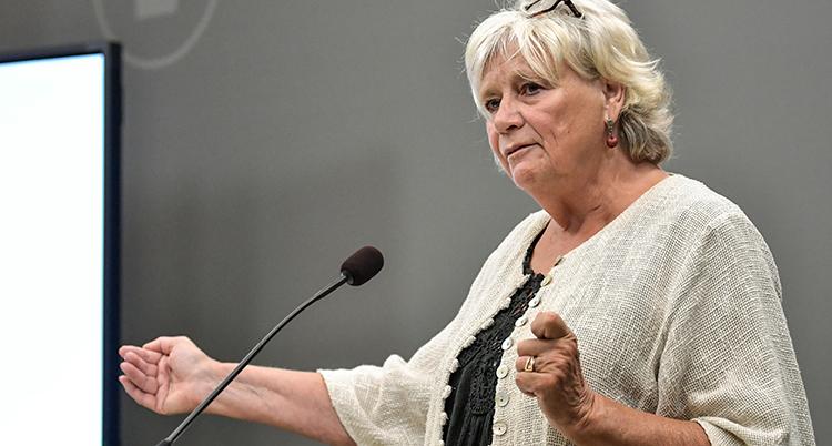 Winberg pratar i en mikrofon. Hon håller ut ena handen i en gest. Hon ser allvarlig ut.