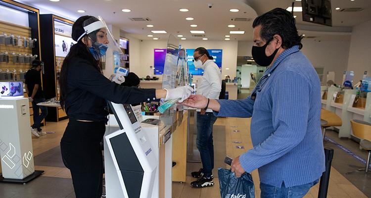 En man i en affär. Han har mask för munnen. Kvinnan bakom disken har munskydd och visir för ansiktet.