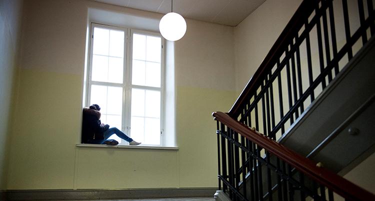 Ett ensamt barn sitter i ett skolfönster och ser ledset ut.