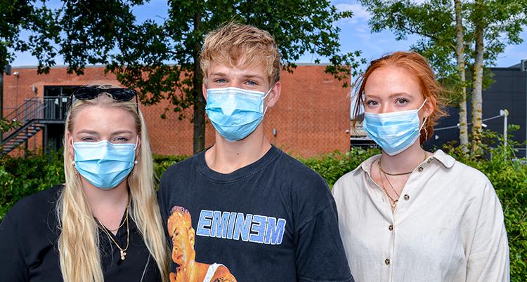 tre unga står bredvid varandra och tittar in i kameran. Alla har ljusblå munskydd.