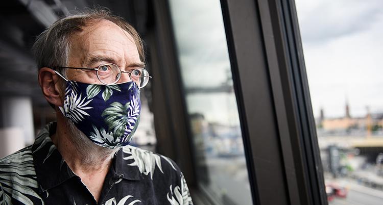 En man tittar ut genom ett fönster. Han ser allvarlig ut. Han har ett blommigt munskydd i blått och vitt.