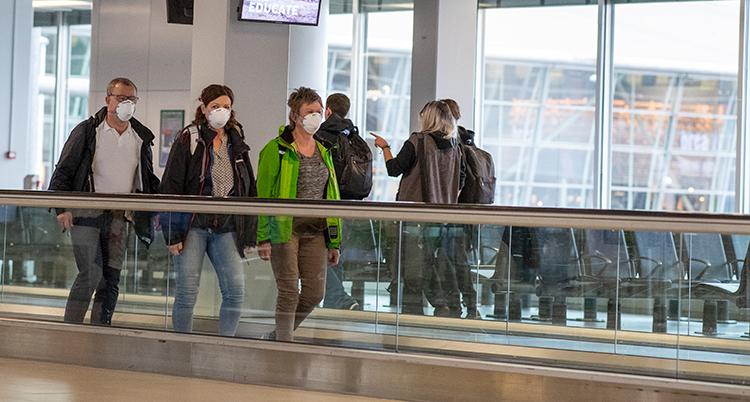 Tre personer har munskydd. De åker på ett rullband på flygplatsen. Bakom dem syns stora fönster.