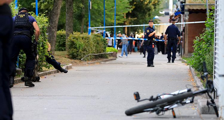 Poliser som står på en gångväg där det skett en skjutning. En cykel ligger på gångvägen.